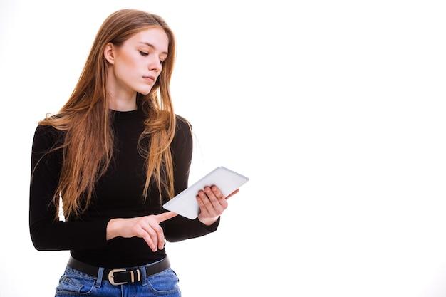Mooi jong meisje met een tablet in studio op een witte achtergrond.