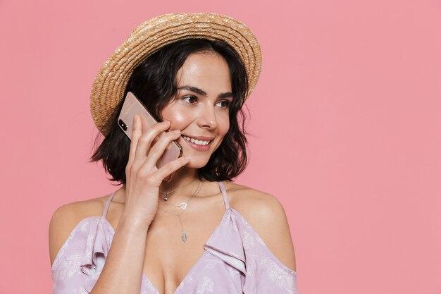 Mooi jong meisje met een zomerjurk die over een roze muur staat en op een mobiele telefoon praat