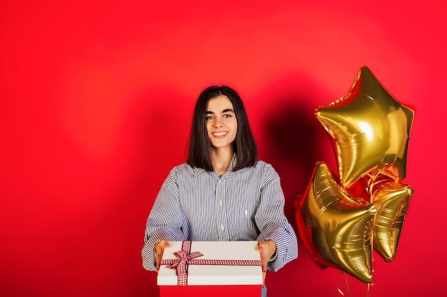 Mooi jong meisje met gouden ballonnen en cadeau op rode achtergrond