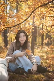 Mooi jong meisje met haar hond in het bos. herfst bos.