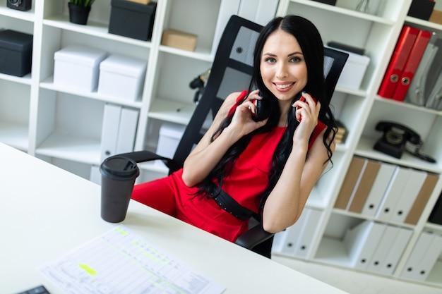 Mooi jong meisje met koptelefoon op nek zitten in kantoor aan tafel.