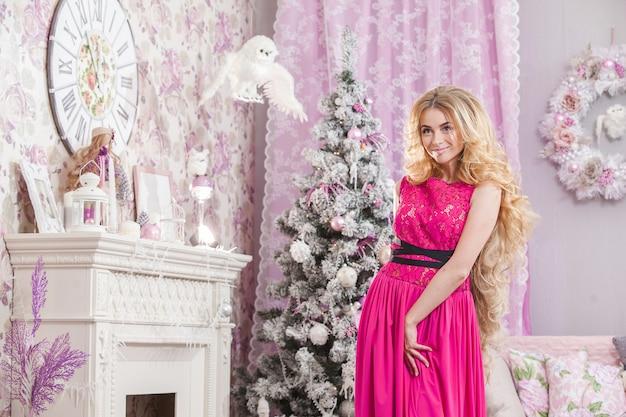 Mooi jong meisje met lang golvend haar in een roze jurk op een achtergrond van de kerstboom