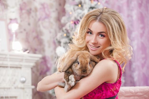 Mooi jong meisje met lang golvend haar in een roze jurk op een achtergrond van een kerstboom met een konijn