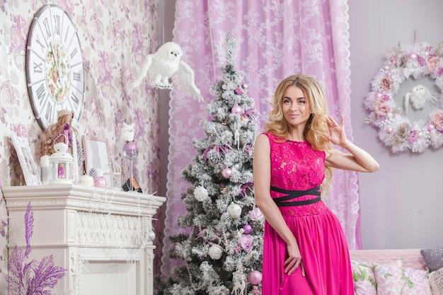 Mooi jong meisje met lang golvend haar in een roze jurk