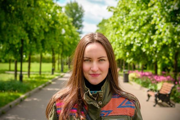 Mooi jong meisje met lang haar en in gekleurd jasje in het de zomerpark.