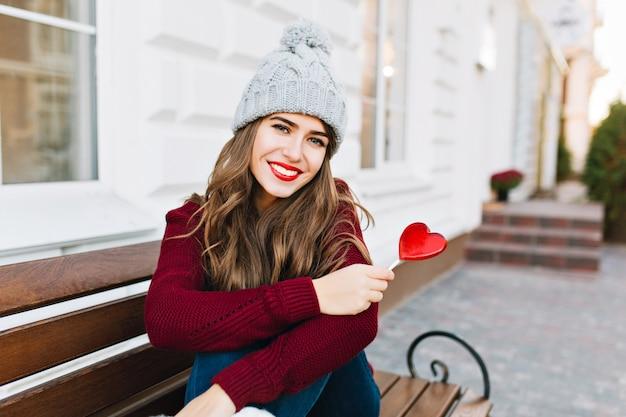 Mooi jong meisje met lang haar in gebreide muts zittend op een bankje op straat. ze houdt een karamelhart vast, glimlachend.