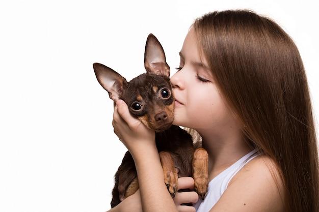 Mooi jong meisje met leuke die terriërhond, op wit wordt geïsoleerd.