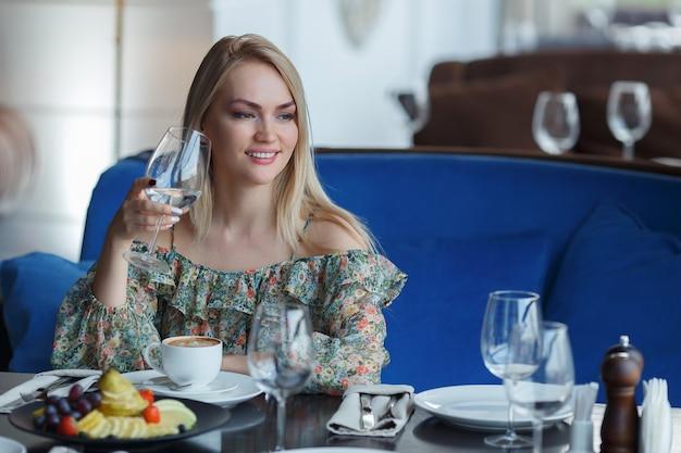 Mooi jong meisje met make-up en kapsel zittend in restaurant met een glas in handen