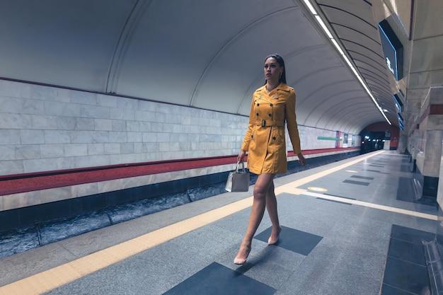 Mooi jong meisje met mooie lange benen in een gele lente jas en een witte handtas op de metro