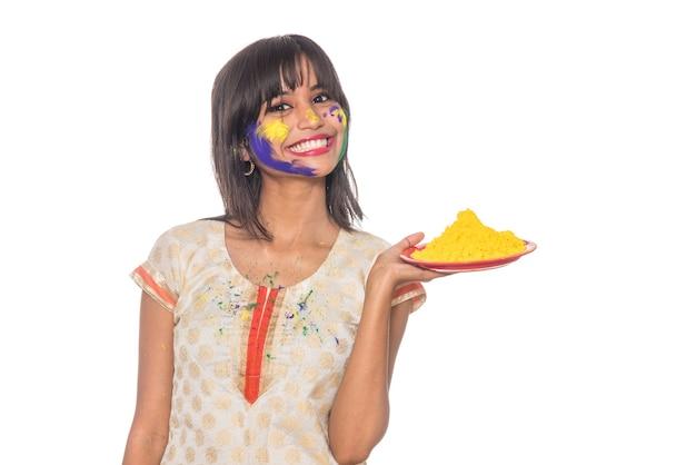 Mooi jong meisje met poedervormige kleur in plaat ter gelegenheid van holi-festival.