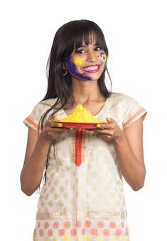 Mooi jong meisje met poedervormige kleur in plaat ter gelegenheid van holi-festival