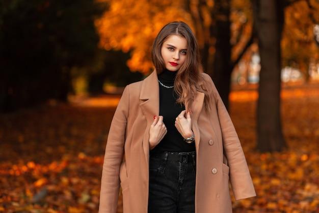 Mooi jong meisje met rode lippen in een modieuze beige jas met een zwarte trui loopt op vakantie in een herfstkleurig park. herfst dames kledingstijl look