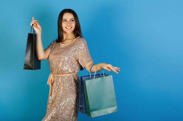 Mooi jong meisje met succesvolle aankopen. glimlachend meisje poseren op blauwe achtergrond.