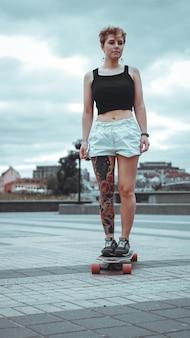 Mooi jong meisje met tatoeages met longboard in de stad. ze heeft een traditionele japanse tatoeage