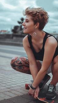 Mooi jong meisje met tatoeages zit op longboard. ze heeft een traditionele japanse tatoeage