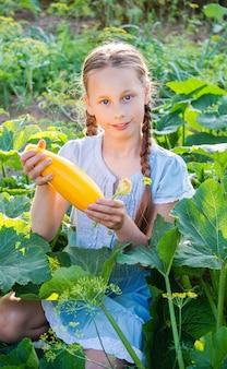Mooi jong meisje met verse gele zuccini in de tuin