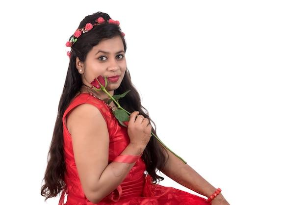 Mooi jong meisje of vrouw die en met rood roze bloem op wit houden stellen