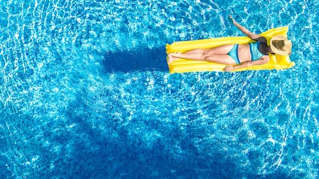 Mooi jong meisje ontspannen in het zwembad, zwemt op opblaasbare matras en heeft plezier in het water op familievakantie, tropische vakantieoord, luchtfoto drone uitzicht van bovenaf