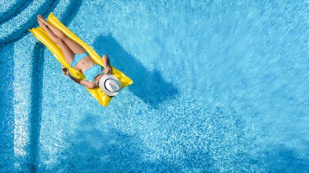 Mooi jong meisje ontspannen in zwembad, vrouw op opblaasbare matras, luchtfoto