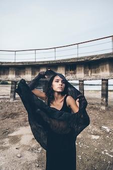Mooi jong meisje op de achtergrond van de dam in een opgedroogd meer in de zwarte swingy rok