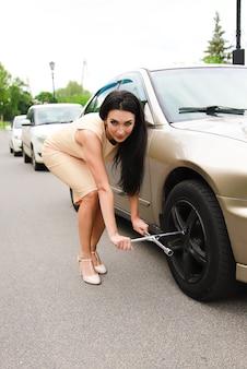 Mooi jong meisje op een achtergrond van een auto en een sleutel voor draaiende wielen
