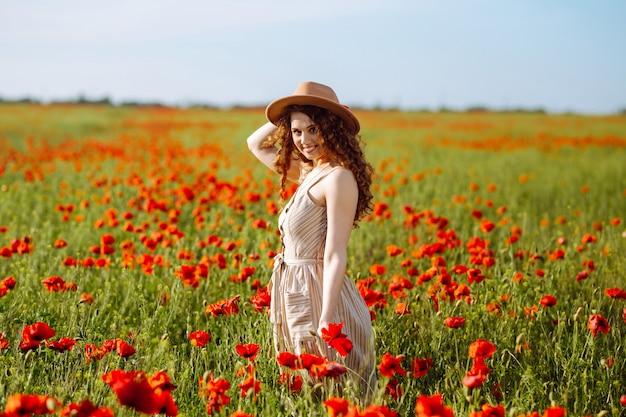 Mooi jong meisje poseren in een papaverveld