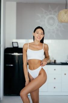 Mooi jong meisje poseren in lingerie in de keuken. mannequin portret in keuken.