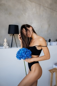 Mooi jong meisje poseren in lingerie in de woonkamer