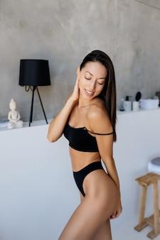Mooi jong meisje poseren in lingerie in de woonkamer.