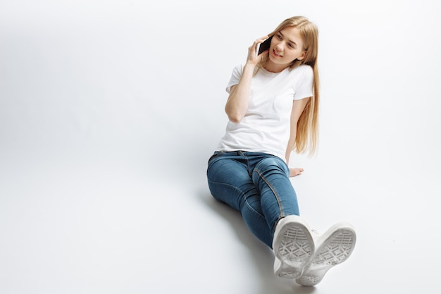 Mooi jong meisje praten aan de telefoon, vrolijk en positief