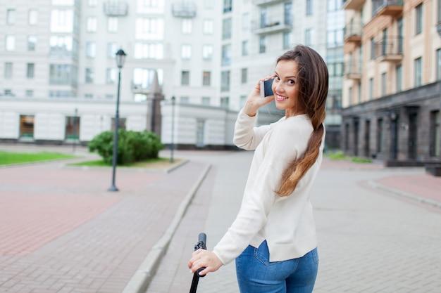 Mooi jong meisje praten met een vriend aan de telefoon.