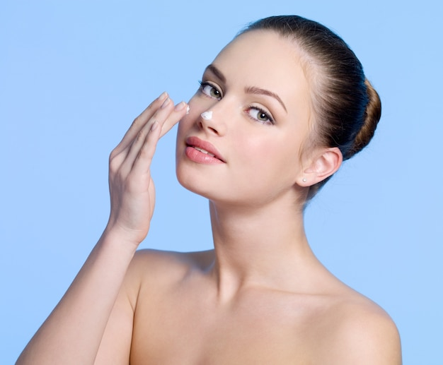 Mooi jong meisje room toe te passen op haar neus op blauw