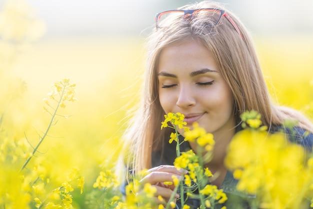 Mooi jong meisje ruikt gele bloemen op een weide met haar ogen dicht, glimlachend.