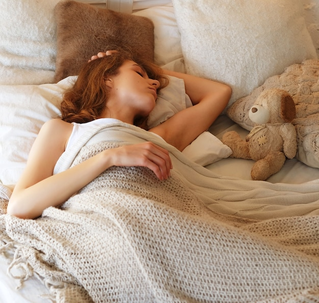 Mooi jong meisje slaapt in de slaapkamer, liggend op bed