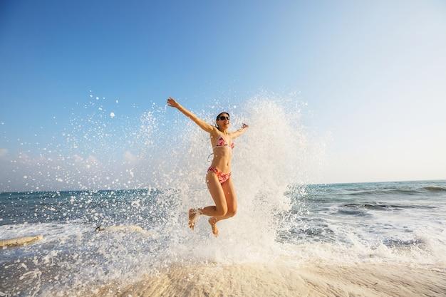 Mooi jong meisje springen op zee