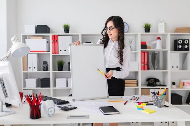 Mooi jong meisje staat in de buurt van een bureau en punten met een pen op een leeg bord