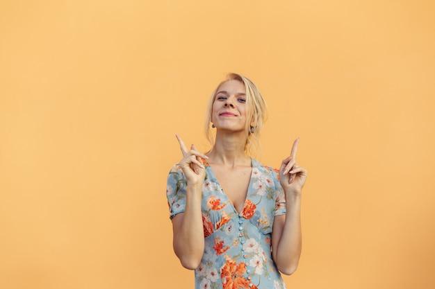 Mooi jong meisje toont vingers naar boven op oranje pastel achtergrond