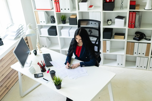 Mooi jong meisje vult de documenten, zittend in het kantoor aan de tafel