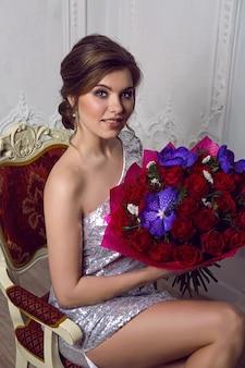 Mooi jong meisje zit op een rode stoel en houdt een groot boeket bloemen vast
