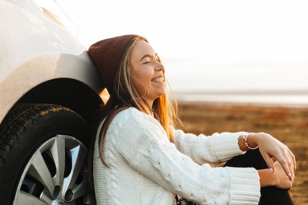 Mooi jong meisje zit op haar auto, zonsondergang kijken