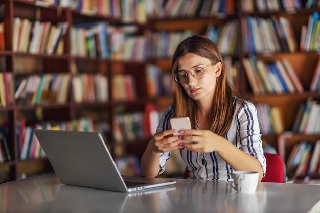 Mooi jong meisje, zittend in de bibliotheek en radeloos met bericht aan de telefoon. ze zou huiswerk op laptop moeten schrijven.