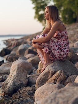 Mooi jong meisje, zittend op de rotsachtige kust in een jurk en kijken naar de zonsondergang