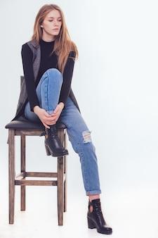 Mooi jong meisje, zittend op een stoel in de studio. met de isolatie.