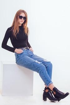 Mooi jong meisje, zittend op een witte kubus in de studio met isolatie.
