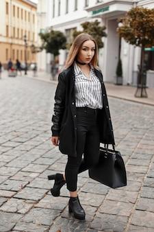 Mooi jong meisjesmodel in een modieuze jas met een zak loopt in de stad