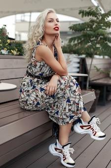 Mooi jong model meisje in een stijlvolle jurk met modieuze sneakers zit op een houten bankje in de straat