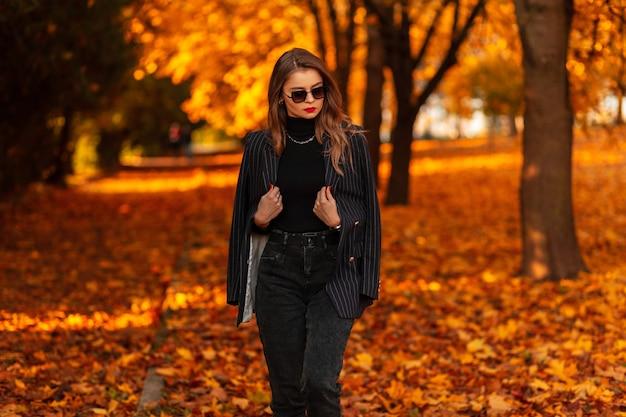 Mooi jong modelmeisje in een elegant pak met een zwarte trui en een blazer loopt in het park met herfstbladeren