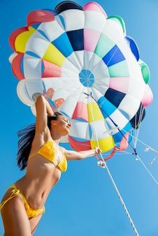 Mooi jong moedermeisje in een zwempak staat op een muur van blauwe lucht en een veelkleurige parachute paragliding en vliegentertainment