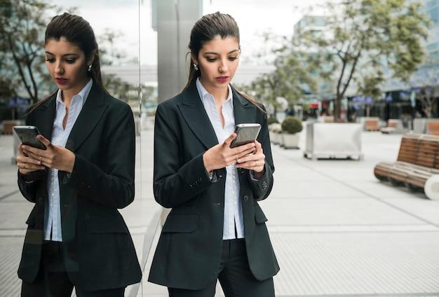 Mooi jong onderneemster het texting bericht op mobiele telefoon die zich dichtbij de weerspiegelende muur bevinden