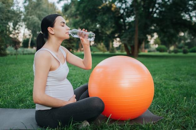 Mooi jong oregnant vrouwen drinkwater in park. ze zit op yogamaatje en houdt een hand op de buik. oranje fitness bal liggen naast.